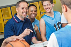 Excited coach and assistant explaining play to basketball player
