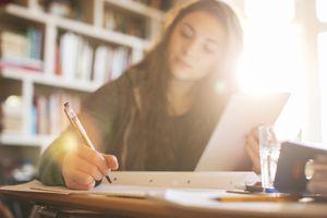 Teenage girl with digital tablet doing homework at sunny desk