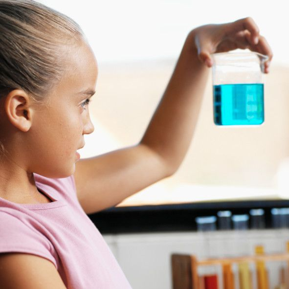 Girl age 10-12 reads the meniscus level on a beaker.