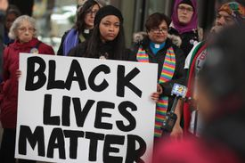 Black Lives Matter protesters carrying signs and speaking to journalists during Women's March.