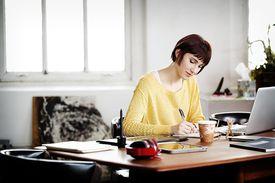 Person writing at desk desk
