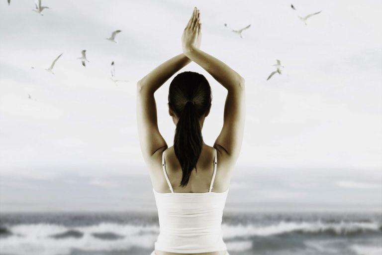 Women meditating on the beach
