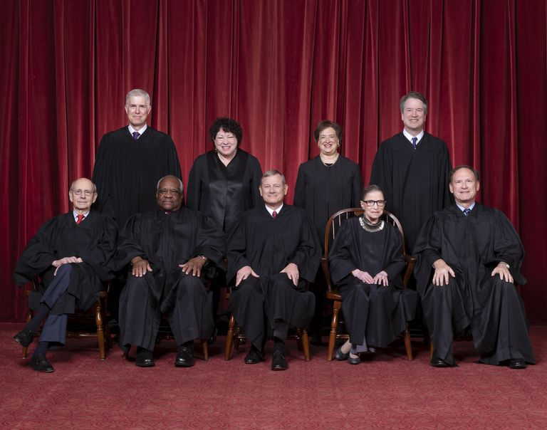 The Supreme Court justices in full robes seated and standing before a red curtain.