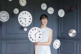 Woman standing with hanging clocks