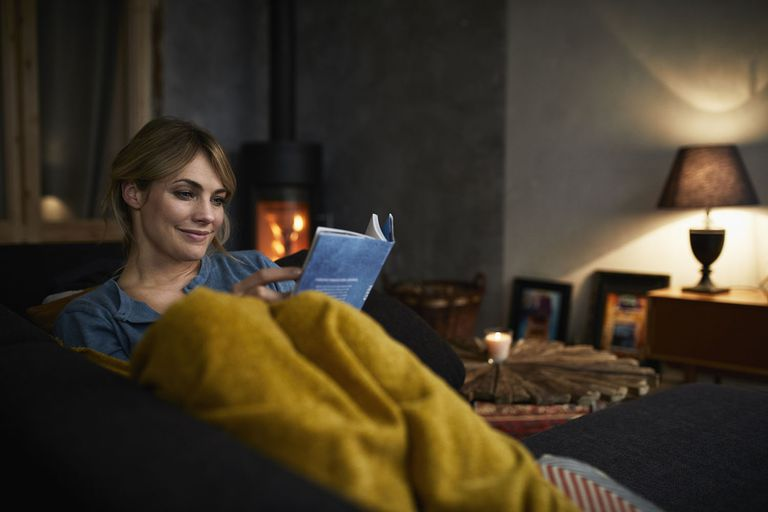 Smiling Woman Reading a Book on Couch at Home in the Evening