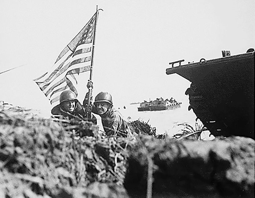 Two soldiers with an American flag on a beach next to a tracked vehicle.