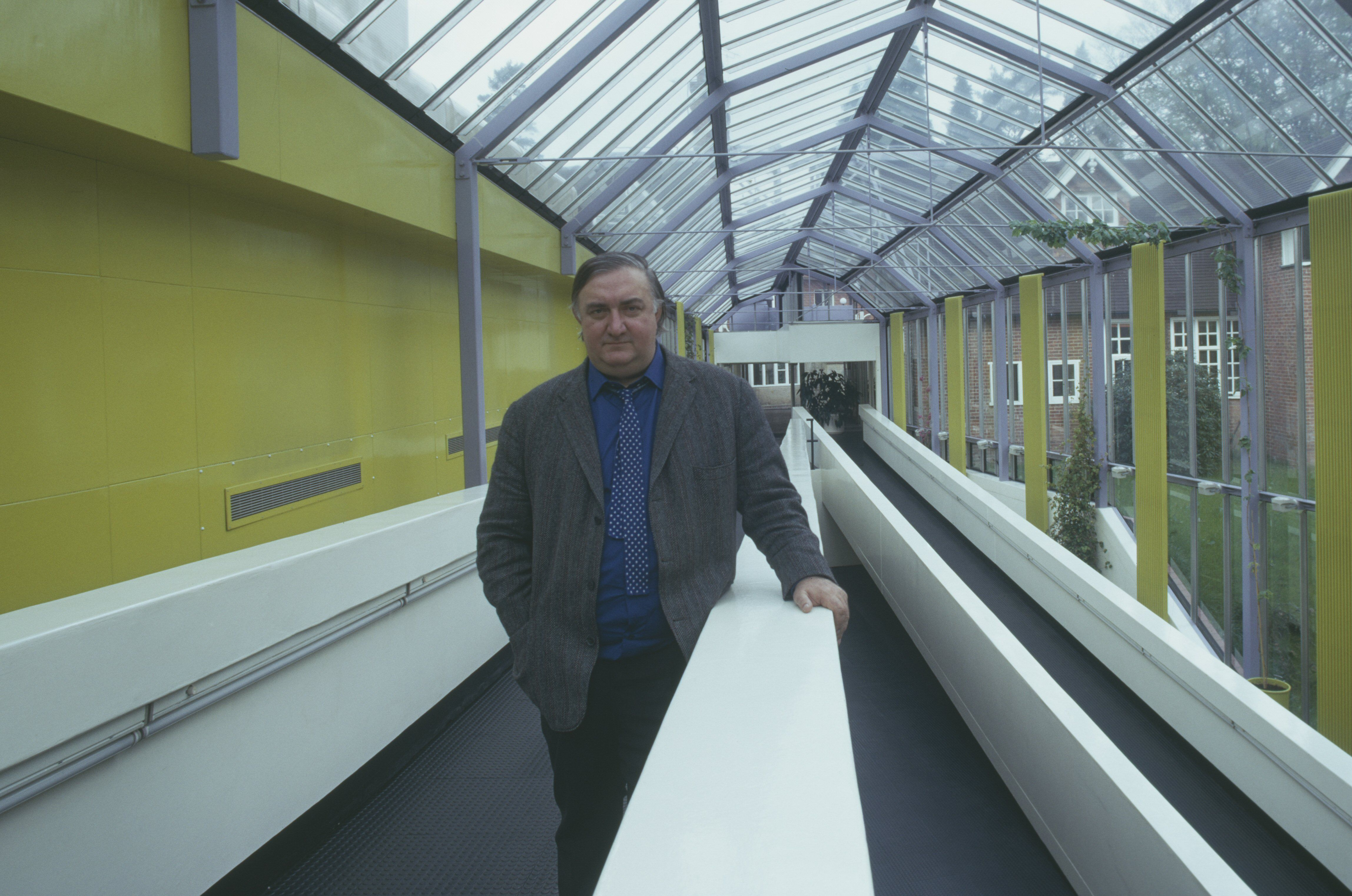 stocky, white man standing in glass-enclosed corridor