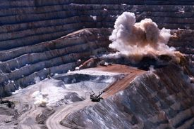 An planned explosion at a copper mining operation with large earth-moving trucks waiting in the foreground.