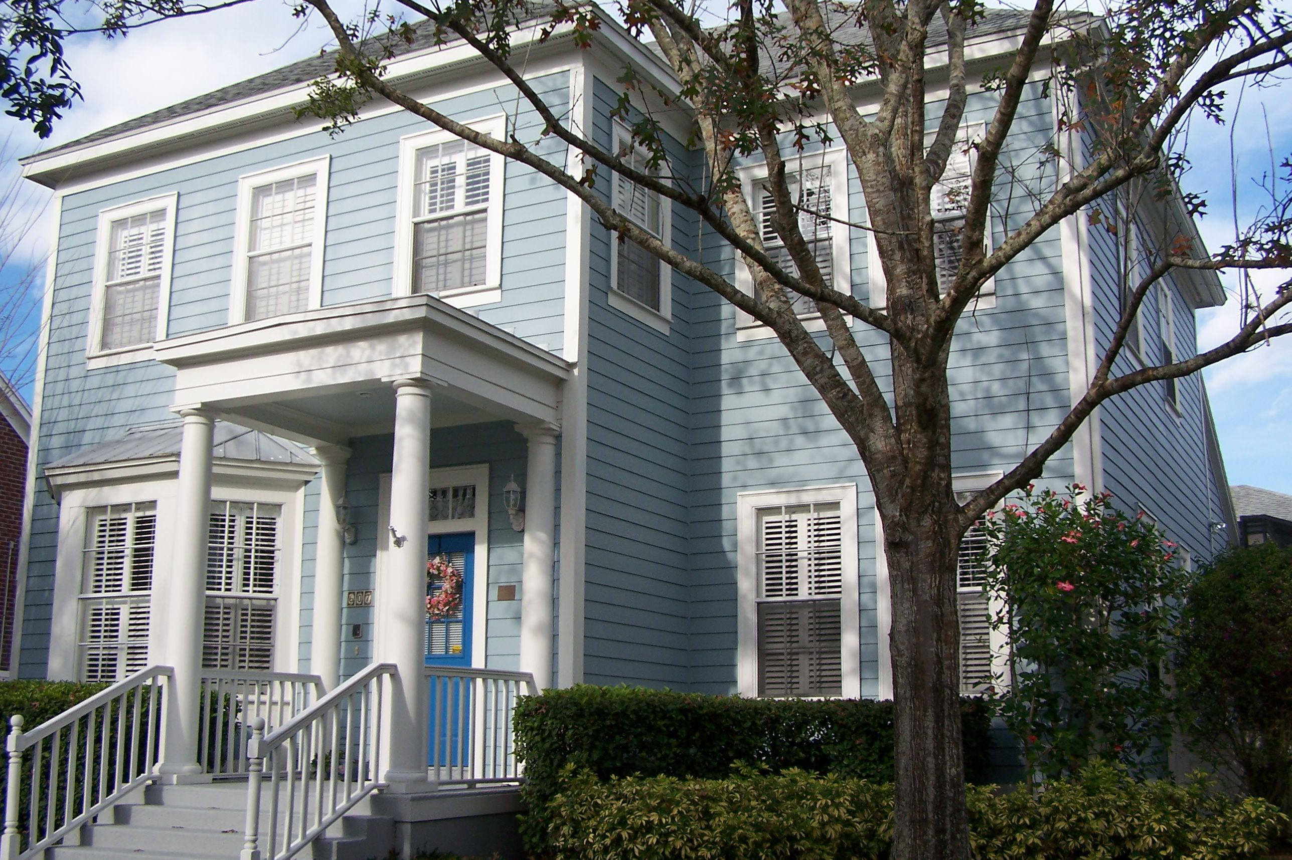 Greek-revival porch on a blue-sided house