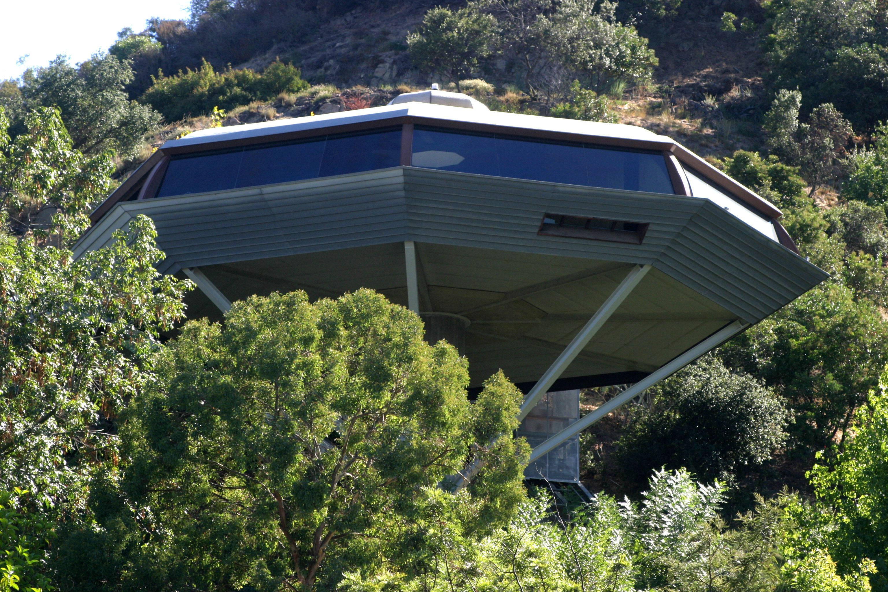 An octagon house that looks like a space ship perched in trees