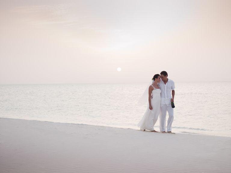 Pareja de recién casados paseando a la orilla del mar.