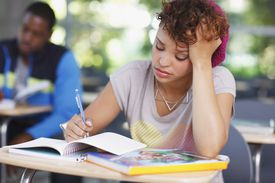 Student with worried expression writing in notebook