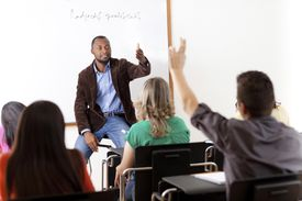 A teacher addressing a student with their hand raised.