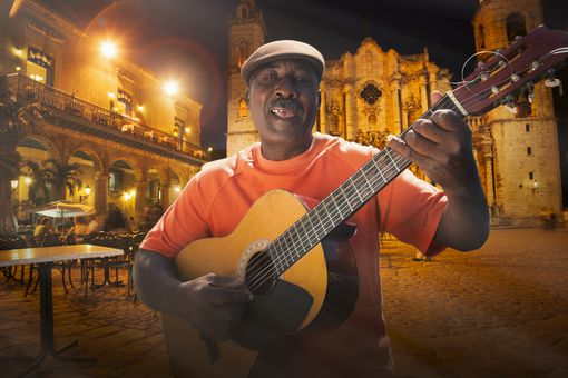 Senior man playing acoustic guitar in Plaza de la Cathedral at night, Havana, Cuba