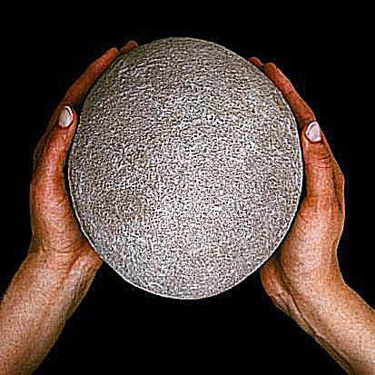 Two hands gently hold a large titanosaur egg