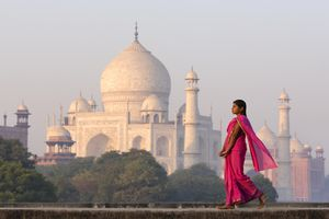 A woman walks along a path with the Taj Mahal in the background