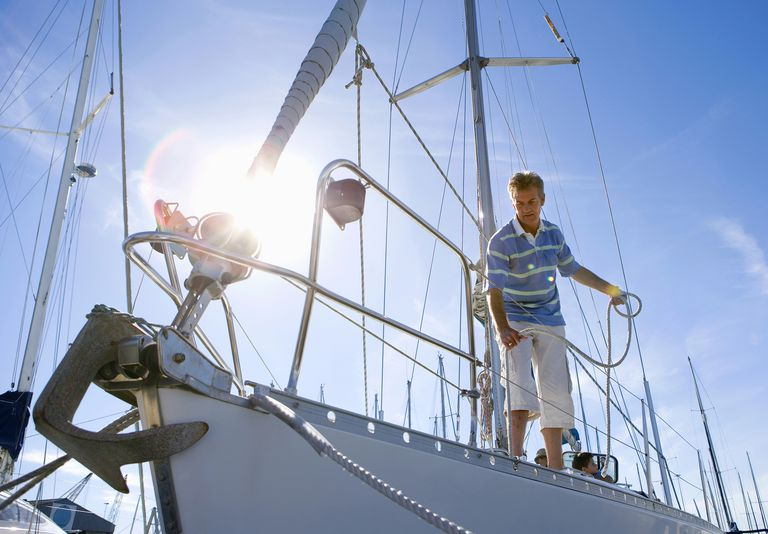 Man standing on deck of moored sailing boat, holding rope