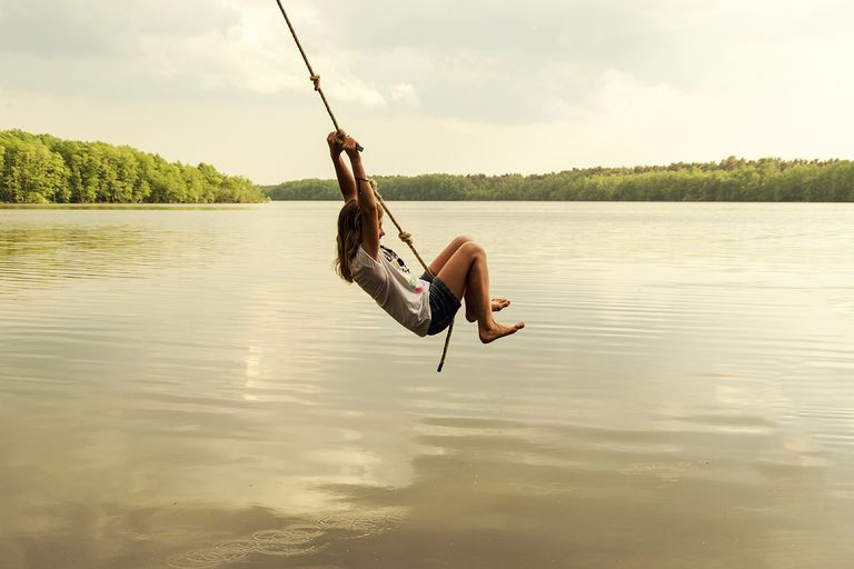 A child on a rope swing above the water