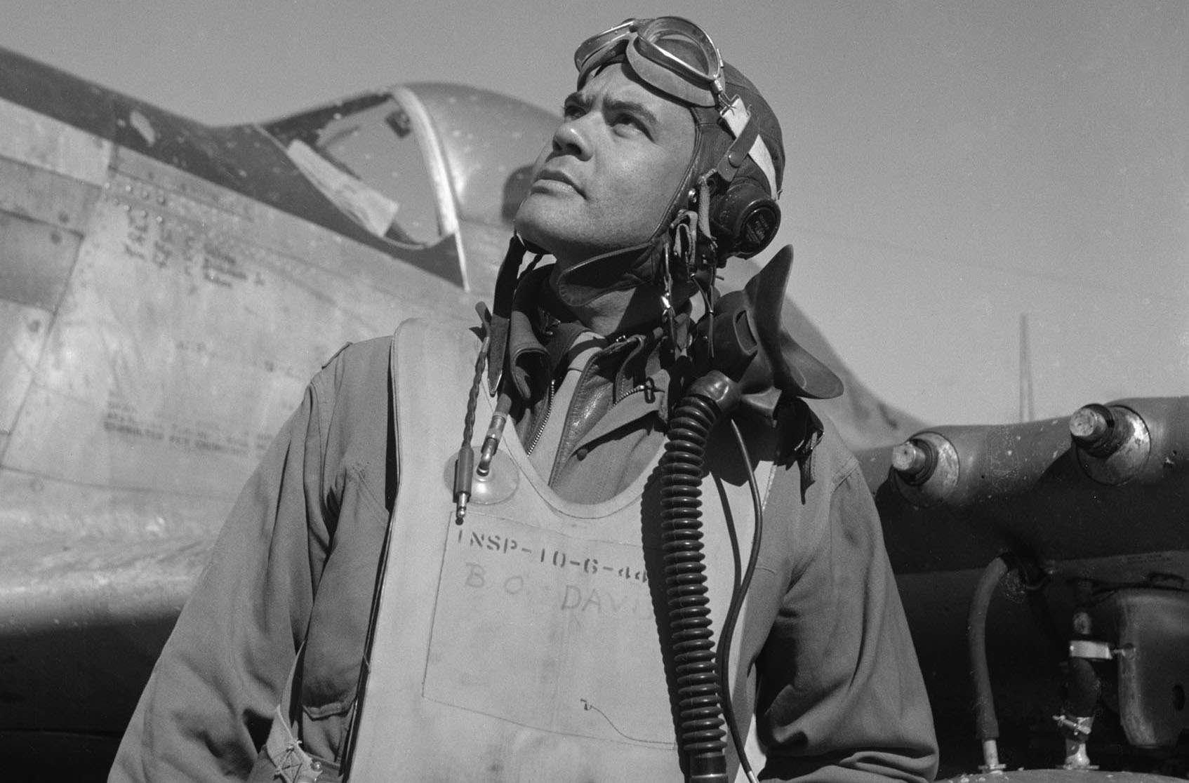 Benjamin O. Davis in a flight suit and helmet standing in front of a P-51 Mustang fighter.
