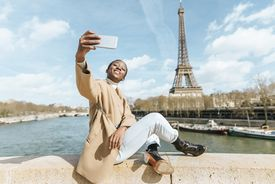 Woman sitting on bridge over the river Seine with the Eiffel tower in the background taking a selfie