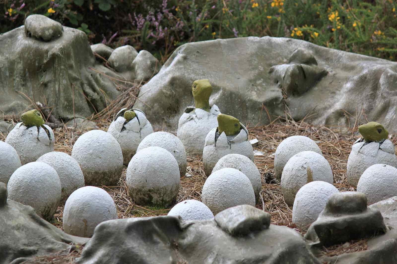 Dinosaur eggs hatching sculpture.
