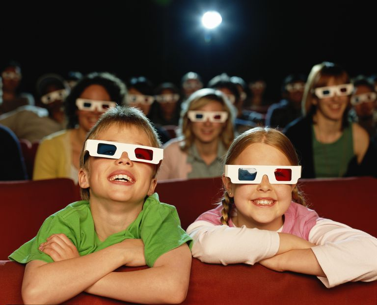 Boy and girl (8-10) in cinema watching 3-D movie, smiling