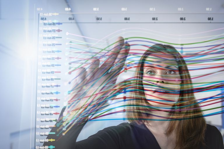Woman standing behind glass with correlating lines on a graph