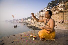 A Brahmin priest prays beside the Ganges River