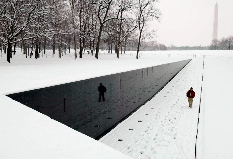 White snowfall intensifies the black granite of the Vietnam Memorial.