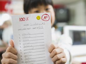 A child holds up a completed spelling test