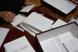 Mature man at desk checking wedding invitations, close up of hands and desk
