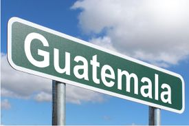 Road sign for Guatemala under a blue sky.