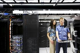 Man and woman looking at computer in server room.