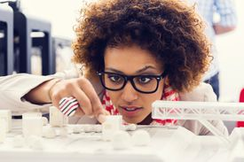Close up of young architect sitting in a 3D printer office and watching 3D printings