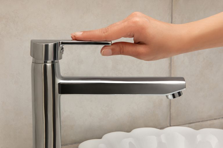 Woman turning faucet off