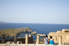 two women overlooking the water, sitting on edge of Greek archaelogical site
