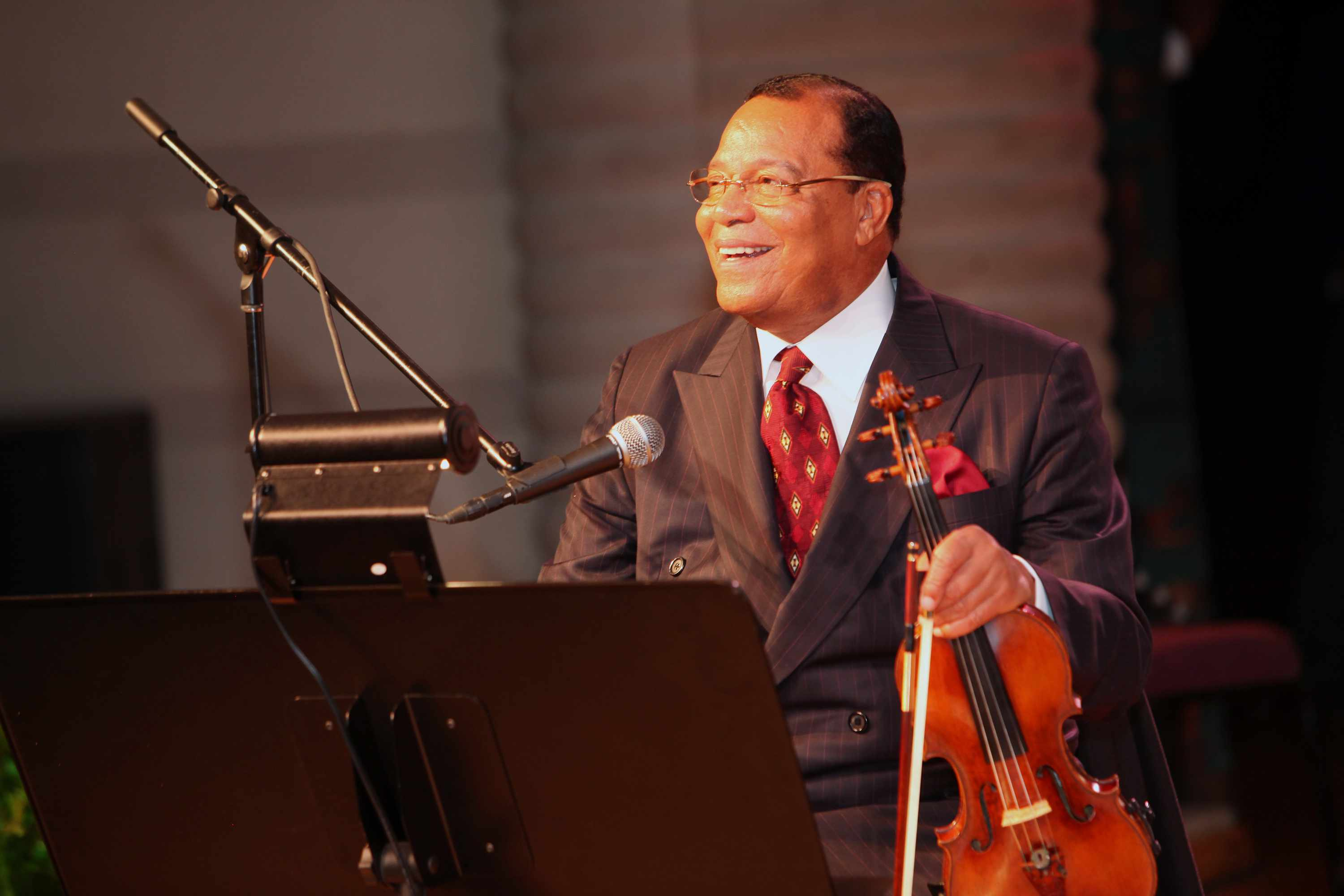 Minister Louis Farrakhan holding a violin and smiling