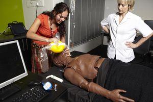 Lecturer observing nursing student performing cpr