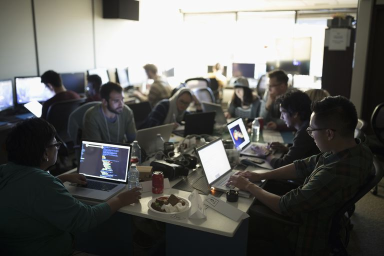 Hackers working hackathon at laptops in dark office