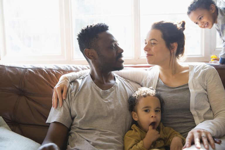 A multi-ethnic family sitting on the couch