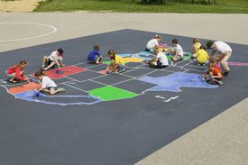 kids drawing map of U.S. in chalk on the ground