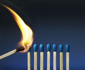 A lit match about light several other blue matches.