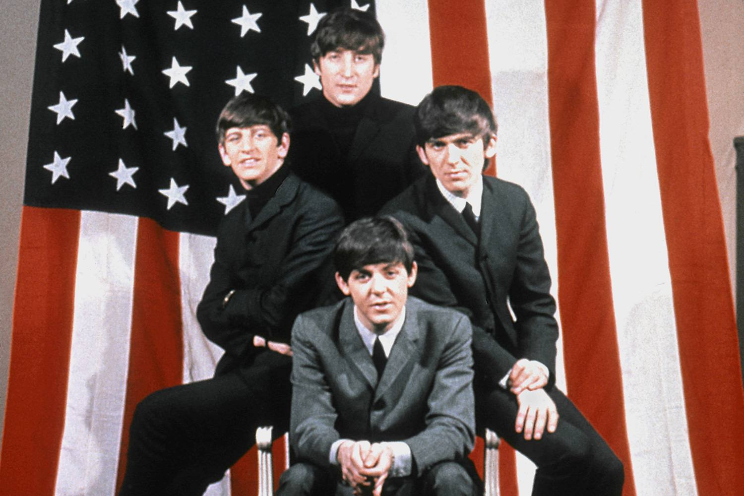 The Beatles color promotional photograph in front of U.S. flag.