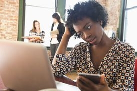 Confused businesswoman using cell phone and laptop in office
