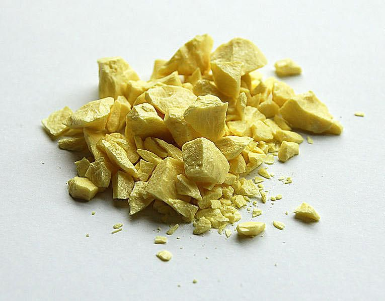 Pile of sulfur against off-white background.