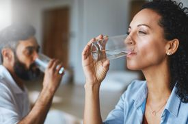 Shot of a couple drinking glasses of water together at home