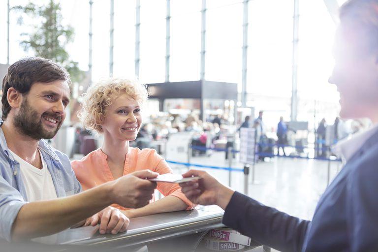 Una pareja mostrando identificación en mostrador de aeropuerto
