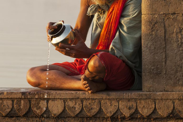 Old man pouring water of holy river Ganges