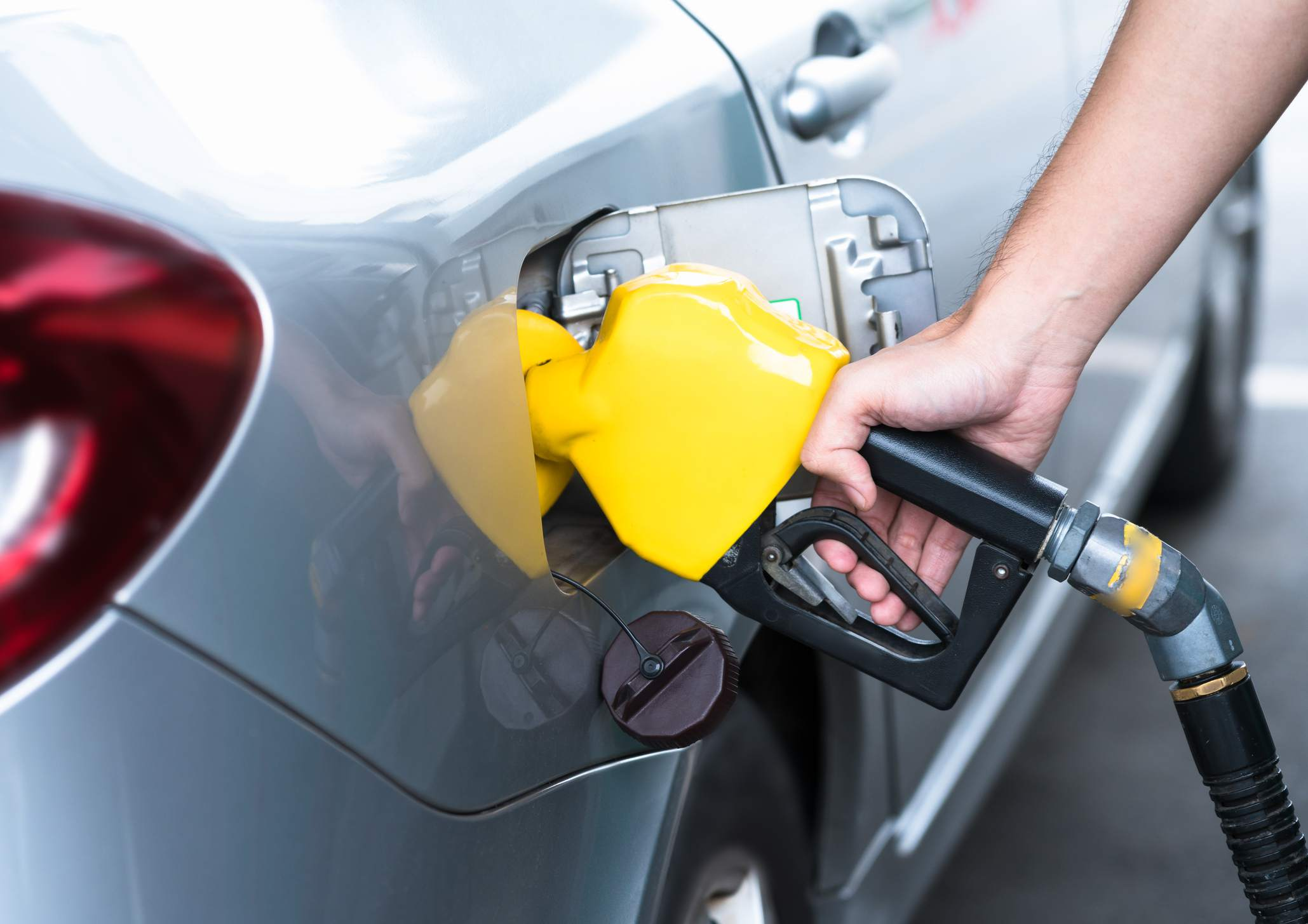 Hand refilling the car with fuel, close-up. - stock photo