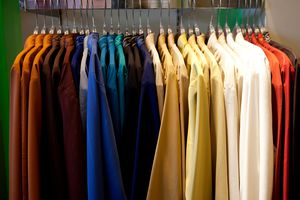 Collared shirts hanging in an color coded row on rack